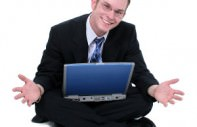 Business Man Sitting On Floor With Laptop Hands Out