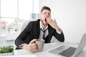 Tired business man yawning at workplace in office